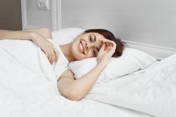 Mujer feliz acostada en su almohada sin dolor de cuello